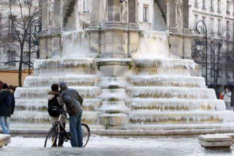 People look at frozen fountain at Place des Innocents as winter temperature fall below freezing point in Paris