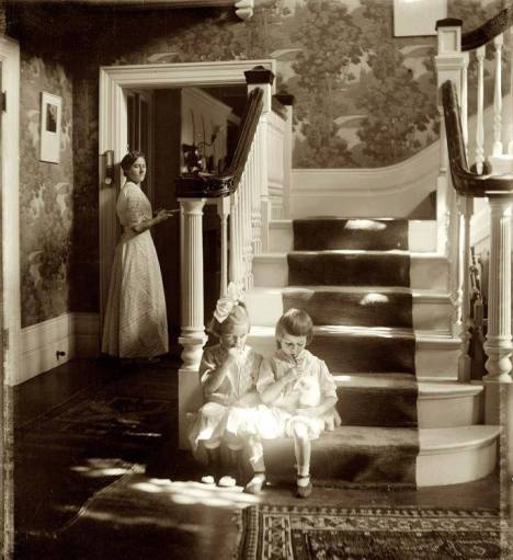 Two girls enjoy sticks of candy and the companionship of their kitty in the warmth of the sunlight. (1910)